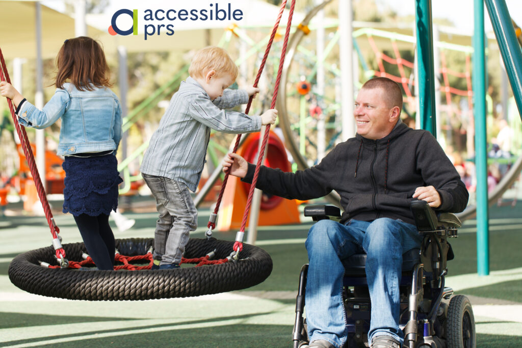 Wheelchair user father plays with his two children in play park